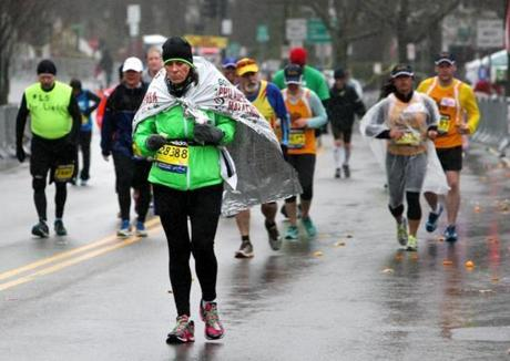 04-20-2015: Newton, MA: Back of the pack runners use a variety of ways to cover up against the rain as they climb Heartbreak Hill in Newton, Mass. during the Boston Marathon April 20, 2015. Photo/John Blanding, Boston Globe staff story/, Sports ( )