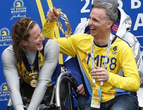 Boston, Massachusetts -- 4/20/2015-- Women's Wheelchair winner Tatyana McFadden shares a laugh with Bill Richard as they pose for pictures at the Boston Marathon Finish Line in Boston, Massachusetts April 20, 2015. Jessica Rinaldi/Globe Staff Topic: Reporter: