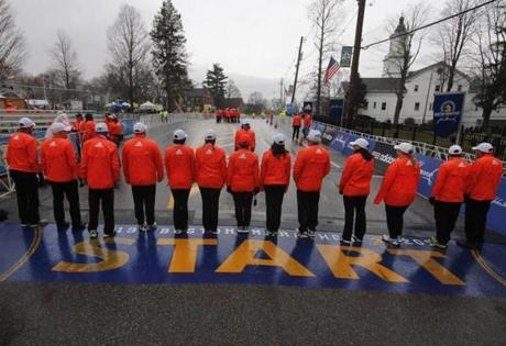 Hopkinton, MA - 4-20-15 - Boston Marathon - Race security personell gather in the drizzle at the start of the Boston Marathon in Hopkinton, MA. (Globe staff / Bill Greene)