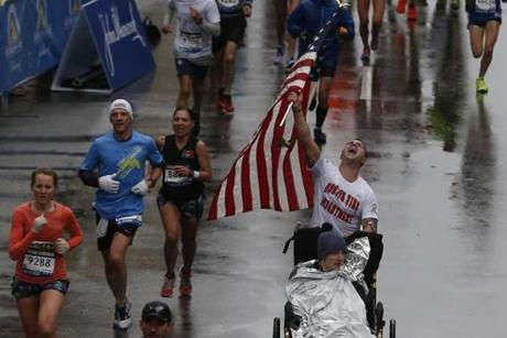 Boston, Massachusetts -- 4/20/2015-- A runner wearing a Boston Fire Department shirt and pushing a man in a wheelchair raises up an American flag before crossing the Boston Marathon Finish Line in Boston, Massachusetts April 20, 2015. Jessica Rinaldi/Globe Staff Topic: Reporter: