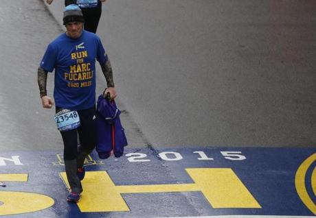Boston, Massachusetts -- 4/20/2015-- William McCabe crosses the Boston Marathon Finish Line wearing a shirt in honor of Boston Marathon bombing victim Marc Fucarile in Boston, Massachusetts April 20, 2015. Jessica Rinaldi/Globe Staff Topic: Reporter: