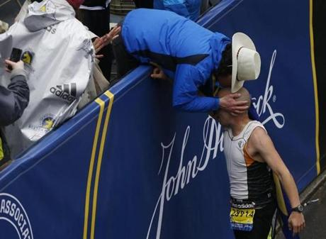 Boston, Massachusetts -- 4/20/2015-- Carlos Arredondo leans over to kiss Robert Wheeler after he crossed the Boston Marathon Finish Line during the 2:49 moment of silence in honor of the Marathon bombing in Boston, Massachusetts April 20, 2015. Jessica Rinaldi/Globe Staff Topic: Reporter: