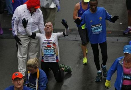 Boston, Massachusetts -- 4/20/2015-- Antonio Jassir falls to his knees to pray after crossing the Boston Marathon Finish Line in Boston, Massachusetts April 20, 2015. Jessica Rinaldi/Globe Staff Topic: Reporter: