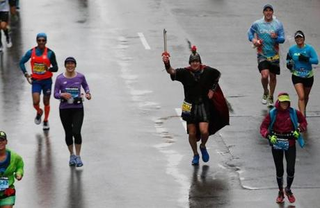 Boston, Massachusetts -- 4/20/2015-- A man in costume leads runners towards the Boston Marathon Finish Line in Boston, Massachusetts April 20, 2015. Jessica Rinaldi/Globe Staff Topic: Reporter: