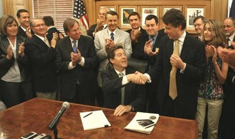 "Governor Sam Brownback of Kansas (seated) in 2012 signed into law one of the largest tax cut bills in Kansas history, saying it would create ""tens of thousands of new jobs."""