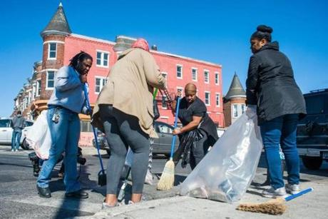 Volunteers cleaned up trash and shattered glass in front of a looted business at the intersection of North Avenue and Fulton Avenue.