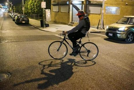 A man gestured Friday as he rode a bicycle during demonstrations in Baltimore.