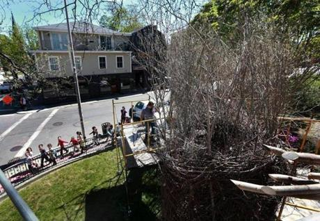 "A group of children looked up at the sculpture ""Stickwork"" as they walked along the sidewalk."