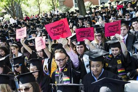 Tufts University graduates held up signs supporting the school's janitors during the commencement ceremony in Medford.