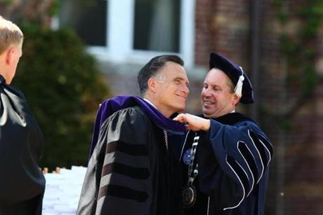 Saint Anselm College president Dr. Steven DiSalvo helped Mitt Romney with his gown at the New Hampshire institution.