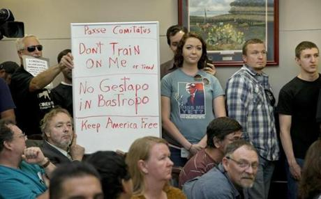 Bob Welch, standing at left, and Jim Dillon held a sign at a hearing about the Jade Helm 15 exercise in Bastrop on April 27T