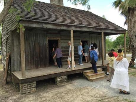 Tourists examine one of the slave cabins.