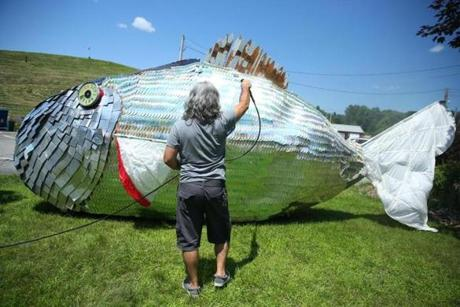 "Fireseed Arts cofounder Patino Vazquez, an artist and musician, gives Moby Disc a bath. The 6,000 ""scales"" on the 30-foot-long sculpture, which makes its home at the Wayland town dump, are discarded compact discs."