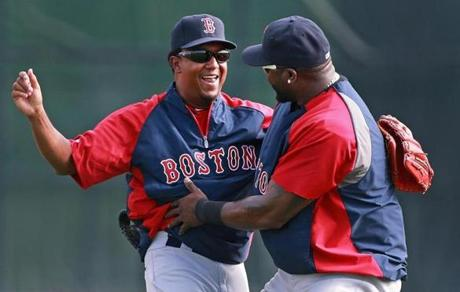 Former Red Sox pitcher Pedro Martinez (left), now a special assistant to the general manager, was warmly greeted by former teammate David Ortiz (right) when they met in the outfield at the start of a morning spring training workout.