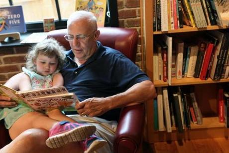 Tom Evans of Whitman read to his granddaughter Sulvie Evans, 3, of Franklin at the bookstore.