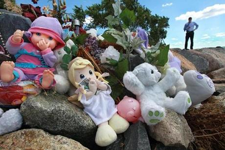 Stuffed animals and dolls are part of a memorial on Deer Island.