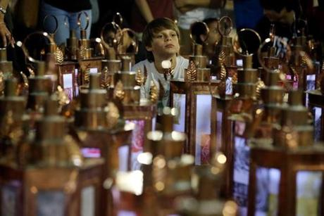 Ben Sutton, 10, sat among the lanterns at the commemorative ceremony at Liberty Tree Plaza in Boston on Friday.