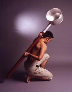 "A man bracing Chien-Wei Chang's ""Huge Ladle"" against his back."