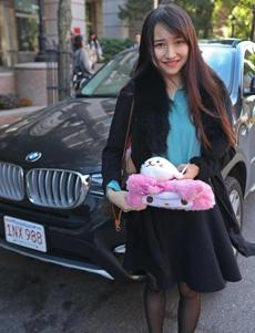 BU student, Tancy Wang from China held her stuffed animal and a tissue box decorated with a little face that she keeps on the dashboard of her BMW parked behind her on Silber Way.