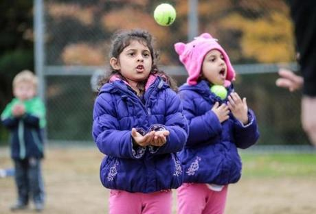 Sophia Ali, 4, (left) and her sister Simal, 4, learn to catch during a tee-ball clinic at Lincoln Park in Lexington.