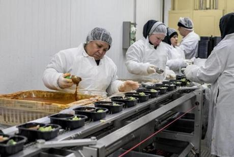 Most of Boston's public schoools rely on frozen entrees trucked in from a food-production facility on Long Island, N.Y., and then warmed up in convection ovens. A plant worker added sauce to lunces destined for Boston's public schools at the Whitsons Culinary Group headquarters in Islandia, New York, Oct. 19.