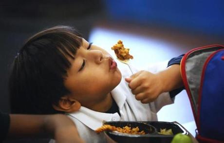Boston, MA--10/21/2015--Kindergartener Moises Montejo (cq) cools off his pasta. School lunches, that were prepared in New York and trucked to Boston, are heated and served at the Blackstone Elementary School/Blackstone Innovation School, on Wednesday, October 21, 2015. Without a true cooking kitchen/cafeteria, the school's lunch area is called a satellite. Photo by Pat Greenhouse/Globe Staff Topic: schoolfood Reporter: James Vaznis