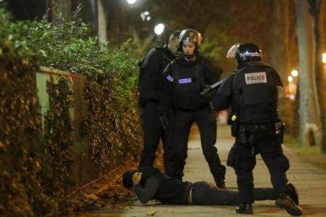 A man lies on the ground as French police check his identity near the Bataclan concert hall. The man was later released after his identity was verified.