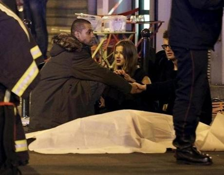 Rescue services personnel worked near the covered bodies outside a restaurant following a shooting incident in Paris.