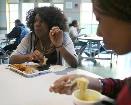 Boston, MA--11/4/2015--Janae Beauliere (cq), 16, left, eats the school lunch, while Imani Joseph (cq), 16, eats noodles in-a-cup from home. Joseph, 16, said she brought her lunch because the school food tastes like