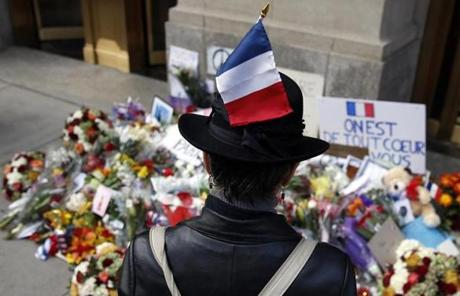 Magali Boutiot, of Providence, who is originally from Toulouse, France paused in front of a makeshift memorial outside of the French Consulate in Boston.