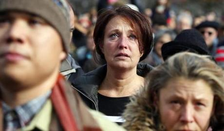 A woman observed a moment of silence for the victims of the Paris attacks.