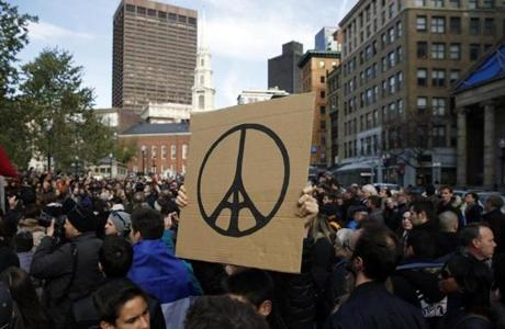 A man held a peace sign with the Eiffel Tower in the center during the rally.