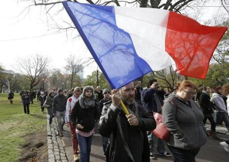 Austin Wolfe, of Quincy, who holds both US and French citizenship, carried a French flag at a vigil Sunday.
