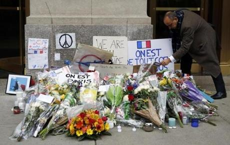 Freland leaned down to read a note at a makeshift memorial outside of the French Consulate.