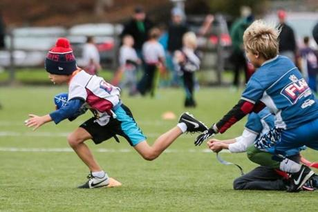 Sam Myerberg, 8, races with the ball during a flag football game.