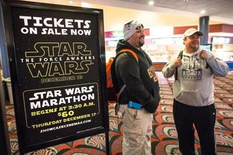 "Michael Greene (left) and Eric Cyphers stood in the lobby of the Showcase Cinema de Lux in Revere near a sign promoting the seven-film ""Star Wars"" marathon."