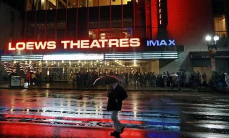Only a set amount of patrons were allowed on the small area of sidewalk outside the AMC Loews Boston Common theater. Once that area was full, patrons waited in the rain across the street on Boston Common.