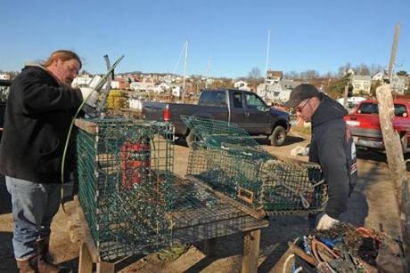 In this photo taken in December 2011, David Sutherland (left) known as Heavy D, and Stephen Redefern repaired steel lobster traps for the fishing boat Trapper Johns at Capt Joe's and Sons in Gloucester, Mass.