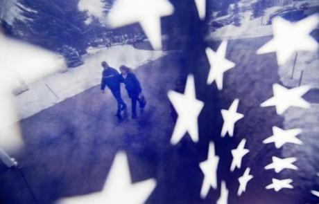 A couple is seen through an American flag as they walked to a polling place in Nashua, N.H.
