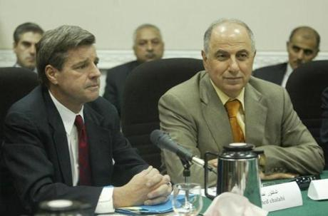 US civil administrator in Iraq Paul Bremer (L) sits next to Ahmad Chalabi, the Pentagon-backed Iraqi National Congress leader, during the 25-member council at the former Ministry of Military Industry in central Baghdad 13 July 2003. Iraq's first national executive body since US-led forces ousted Saddam Hussein and his Baath Party more than three months ago gathered in Baghdad for a landmark meeting which falls almost 35 years to the day after the Baath Party regime came to power in 1968. AFP PHOTO/Marwan NAAMANI/POOL (Photo credit should read MARWAN NAAMANI/AFP/Getty Images)