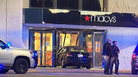 The suspect crashed his car into the entrance of a Macy's after stabbing two women at a home nearby, authorities said.