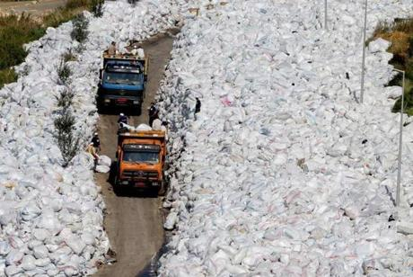 Rubbish trucks drive between a built up pile of waste on a street in Beirut's northern suburb of Jdeideh in February.