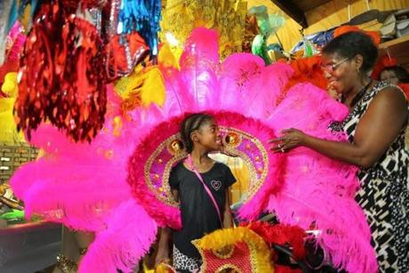 Juliana Osborne helped Madison Joseph, 8, with a large headdress that will be used during Carnival Day events Saturday in Dorchester.