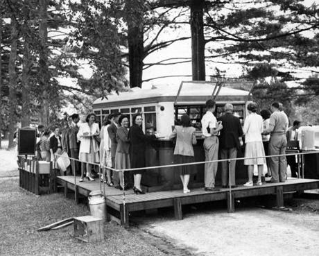 Stockbridge, MA - 7/1/1946: Lunch is served from a school bus remodeled into a mobile cafeteria and backed up to a platform with ramps at Tanglewood, summer 1946. [Date unknown - estimated to month] (Charles F. McCormick/Globe Staff) --- BGPA Reference: 170216_EF_007