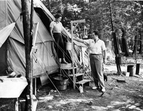 Stockbridge, MA - 8/1/1939: One of the tents in which a group of Boston Symphony Orchestra are camping during the Berkshire Symphonic Festival at Tanglewood, August 1939. Mrs. Rene Voisin takes a pail of Lake Makheenac water from her son, Roger, of the orchestra. Most of the orchestra members choose hotels, or cottages for the 12 to 14 days' stay in the heart of the Berkshire, but a few prefer camping. [Date unknown - estimated to month] (Boston Globe Archive/Unknown) --- BGPA Reference: 170216_EF_001