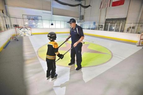 Joe Dellanno, president of Smart Light Sports, works with Patrick Sweeney, 9, of Wakefield, who us autistic, during a session that mixes hockey, light therapy and visual imprinting. Josh Reynolds for The Boston Globe (WeWk, healey)