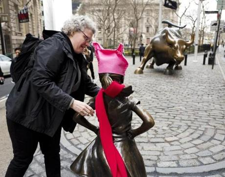 "A woman places a red scarf on a statue of a fearless girl facing the Wall Street bull, Wednesday, March 8, 2017, in New York. The statue was installed by an investment firm in honor of International Women's Day. An inscription at the base reads, ""Know the power of women in leadership. She makes a difference. State Street Global Advisors."" (AP Photo/Mark Lennihan)"