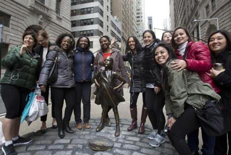 A group of women stop to pose with a statue of a fearless girl, Wednesday, March 8, 2017, in New York.