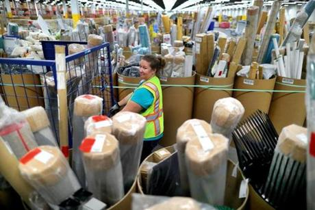Worker Kathleen Frey loads a cart with cutomer orders from rows and rows of items stored in tubes.