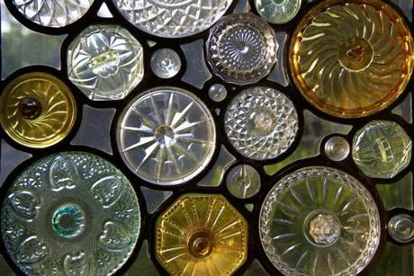 Above,  a stained-glass  window made from Depression-era  candy jar lids. It was designed and fabricated by artist Dan Maher.